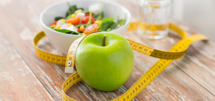 healthy eating, dieting, slimming and weigh loss concept - close up of green apple, measuring tape and salad